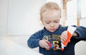 Criança segurando escova de dentes e creme dental