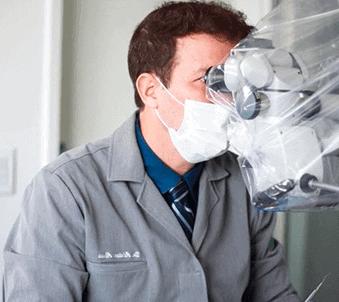 Dr Adriano Abreu usando microscópio odontológico